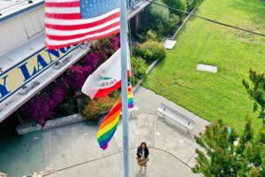 woman raising flag on school campus